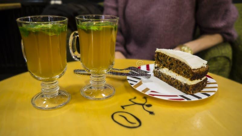 Ljust rödbrun te och en skiva av morotkakan arkivfoto
