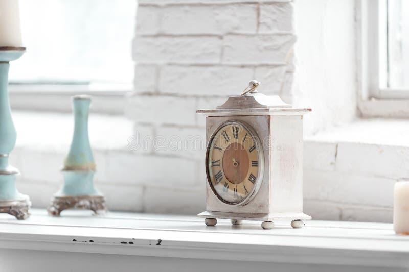 Ljust sjaskigt chic inre fragment med klockan och ljusstakar royaltyfri bild