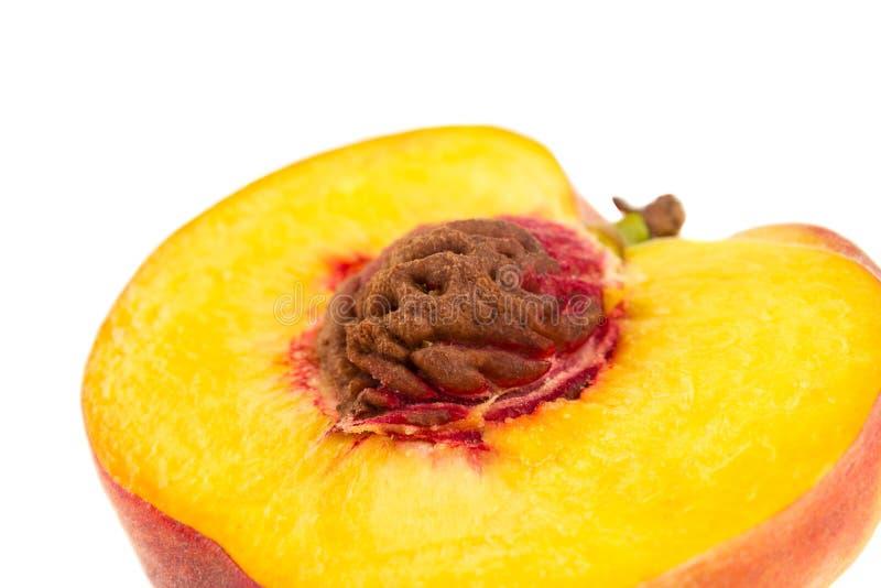 Ljust slut upp halva av en persika med den skarpa gropen som isoleras på vit royaltyfria bilder