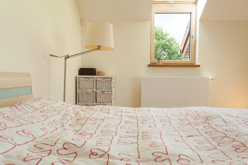 Ljust sovrum med det lilla fönstret arkivfoto