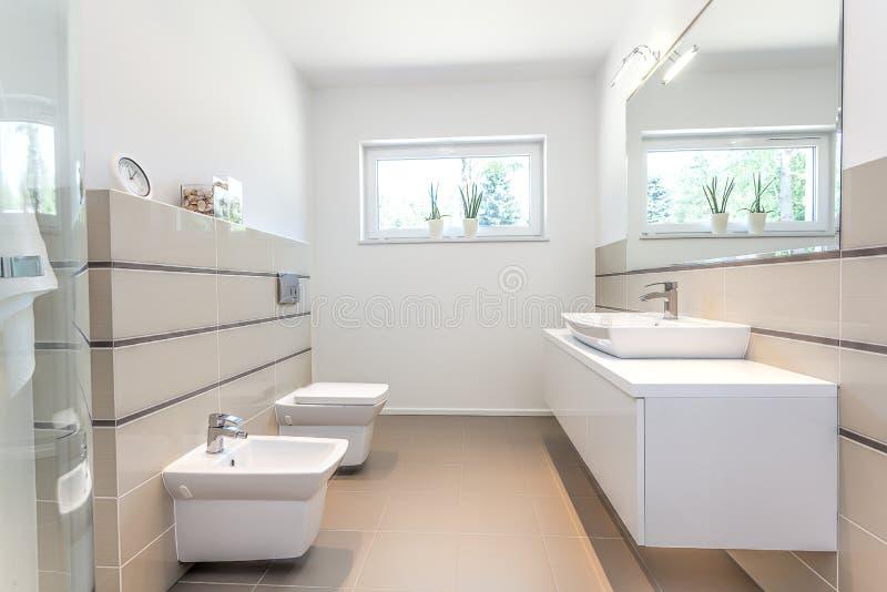Ljust utrymme - vitt badrum arkivbild