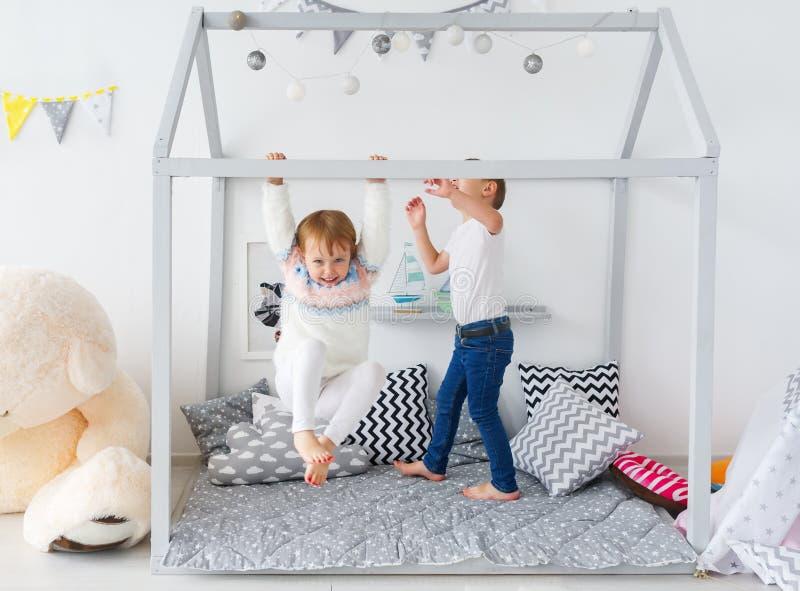 Ljuv lek för små barn i barnkammarerummet arkivfoto