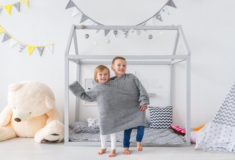 Ljuva små barn i stor grå tröjalek i barnkammaren hyr rum arkivfoton