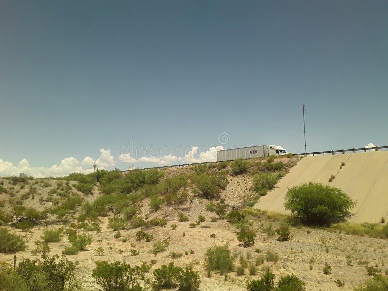 LKW überschreitet über eine Überführung mit den Wolken, die scheinen, hinten vom Zug zu strömen stockfotografie