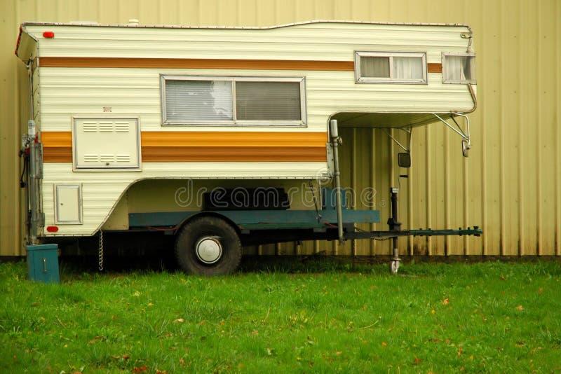 LKW-Bettwohnmobil mit Wand und Gras stockfotografie