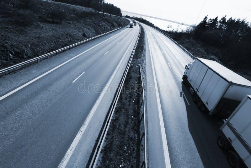 LKW, der auf Autobahn an der Dämmerung fährt stockbilder