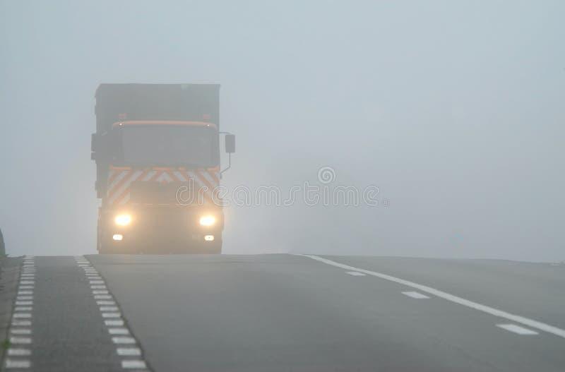 LKW, der ein durch Nebel mit Scheinwerfern erscheint stockfoto