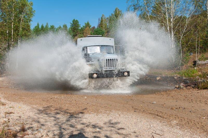 LKW-Durchläufe durch eine Pfütze lizenzfreies stockfoto