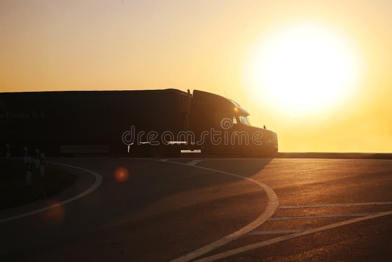 LKW geht auf Landstraße auf Sonnenuntergang stockbilder