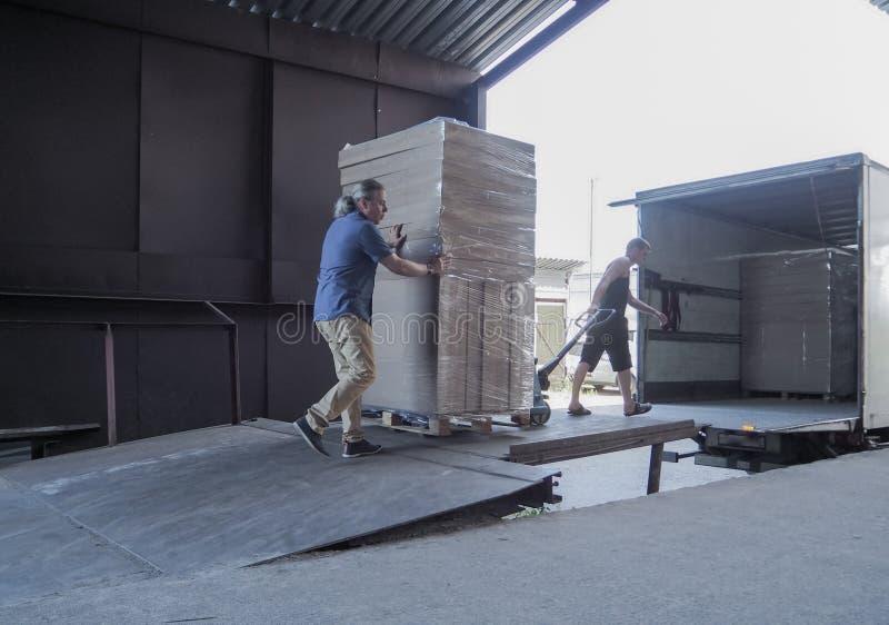 LKW-Laden und -Versand Männliche Arbeitskräfte laden die Waren in den Pappschachteln auf einem LKW lizenzfreie stockbilder