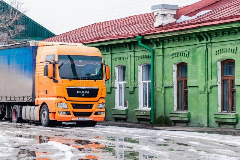 LKW-Marke Mann Russlands Kemerovo 2019-03-15 mit gelben Kabinenständen nahe dem grünen alten Weinlesehaus mit rotem Dach Konzept lizenzfreie stockfotografie