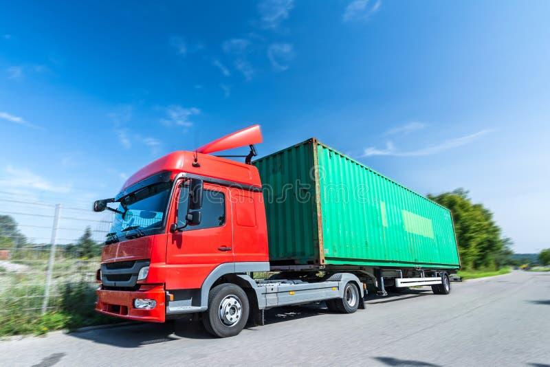 LKW mit Behälter auf dem Anhänger fährt auf die Straße stockfotos