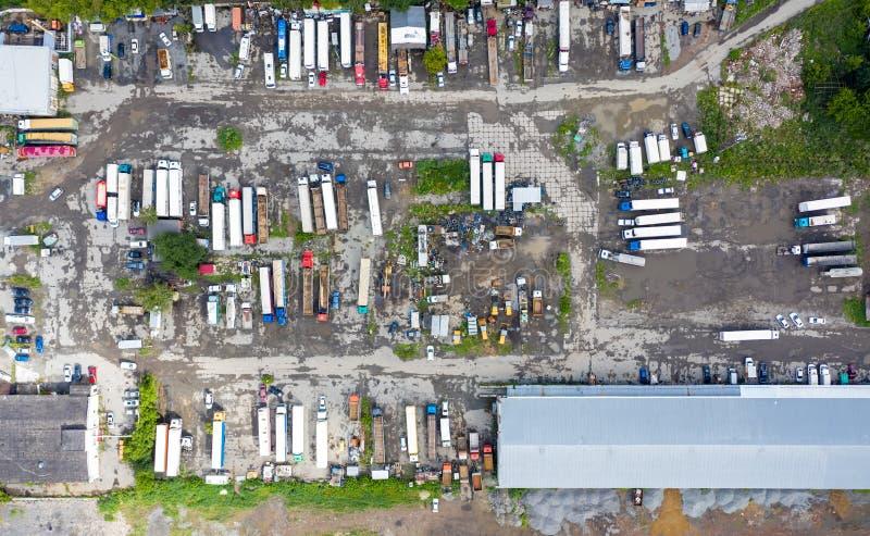 Lkw-Parkplätze und andere Fahrzeuge im Industriegebiet, Sommer, Grasasphalt, Hangarantensicht von oben Lastkraftwagen beim Verlad stockfotografie