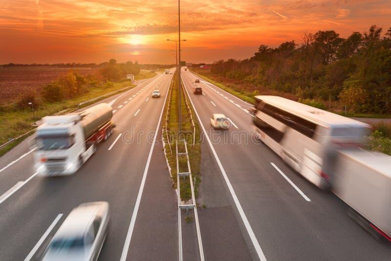 LKW und Bus auf der Autobahn bei Sonnenuntergang lizenzfreies stockfoto