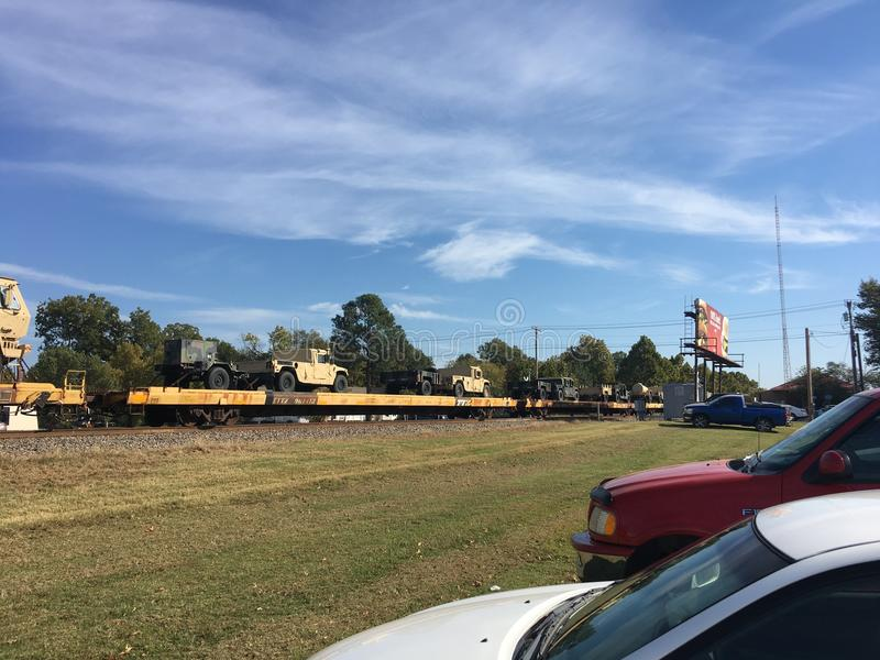 LKWs der AMERIKANISCHEN Armee auf der Eisenbahn, die durch Schiene transportiert wird lizenzfreie stockfotos