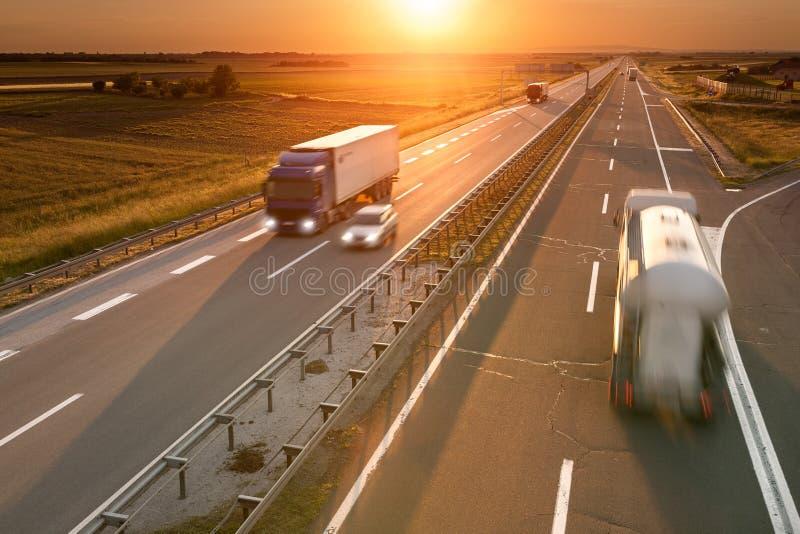 LKWs und Auto auf der Autobahn bei Sonnenuntergang lizenzfreie stockbilder