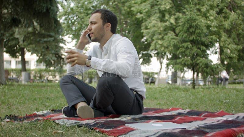 Llámeme en cualquier momento Hombre joven alegre que habla en el teléfono que se sienta en la hierba en el parque imagen de archivo libre de regalías