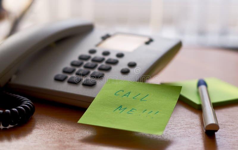 llámeme nota-etiqueta engomada en un teléfono fotografía de archivo