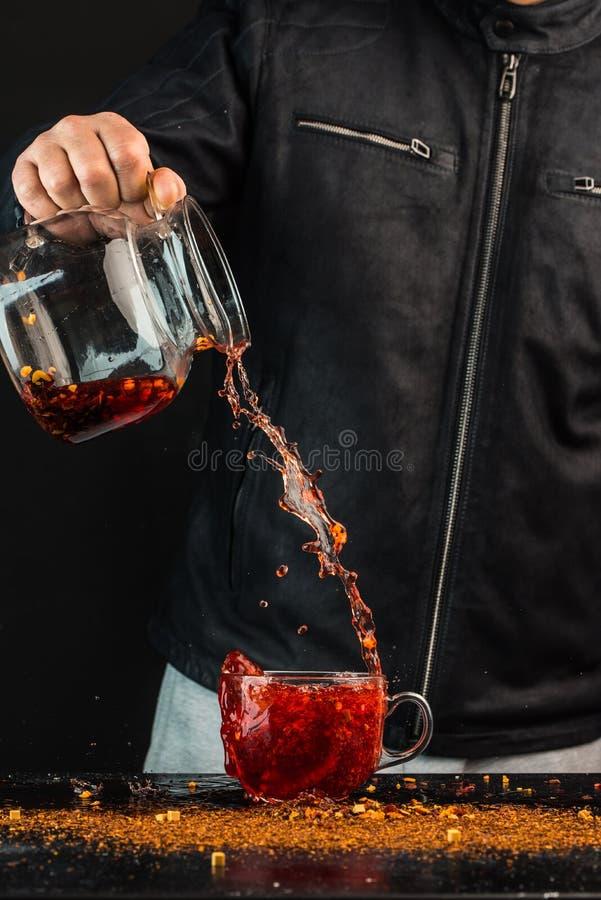 Llénese encima de - un hombre vierte una bebida de un jarro en una taza de cristal, usted puede ver descensos y un chapoteo líqui fotos de archivo