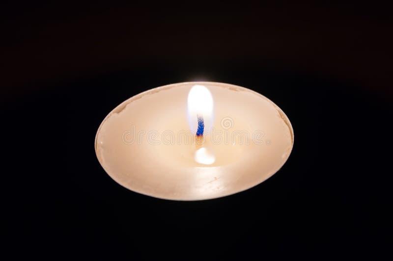 Llama de la vela blanca en la noche imagen de archivo
