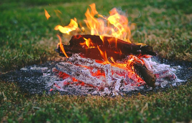 Llama de un fuego que quema en la noche oscura y los carbones ardientes que dan calor al hogar en el salvaje imagen de archivo libre de regalías