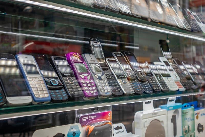 Llama por teléfono al escaparate de la tienda directa nueva y retra Evolución de los móviles del telclado numérico al panel tácti foto de archivo libre de regalías