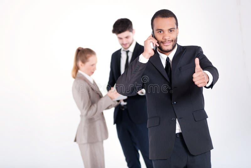 Llamada acertada del negocio Negocio africano acertado y sonriente foto de archivo