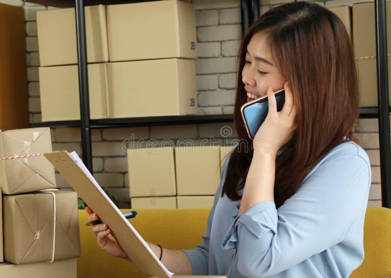 Llamada asiática del smartphone del uso de la mujer de negocios al cliente para escribir el producto de la orden con la cara feli fotografía de archivo