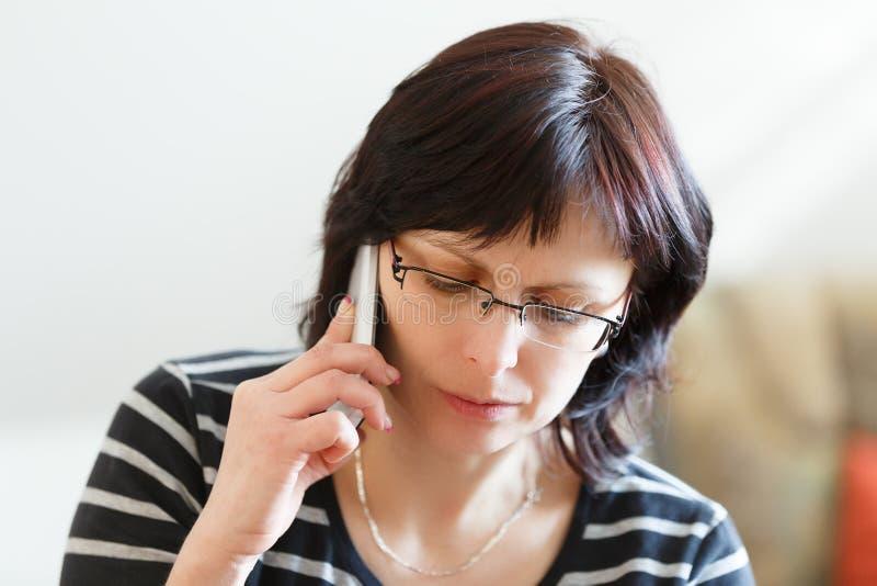 Llamada de mediana edad cansada de la mujer por el teléfono fotografía de archivo