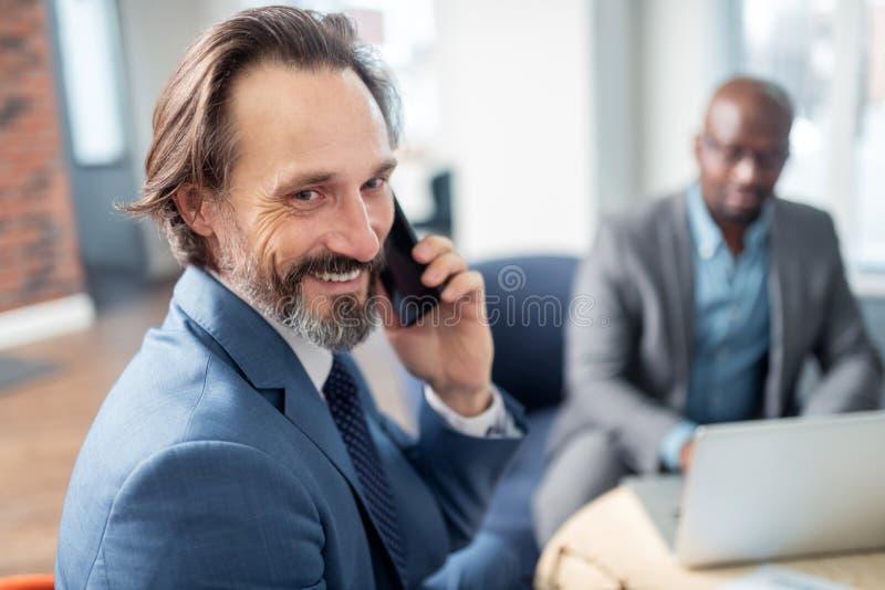 Llamada de recepción feliz de la sensación del hombre de negocios de la esposa mientras que trabaja fotos de archivo libres de regalías
