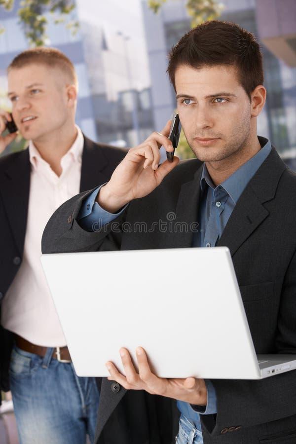 Llamada de teléfono de fabricación ocupada de dos hombres de negocios foto de archivo