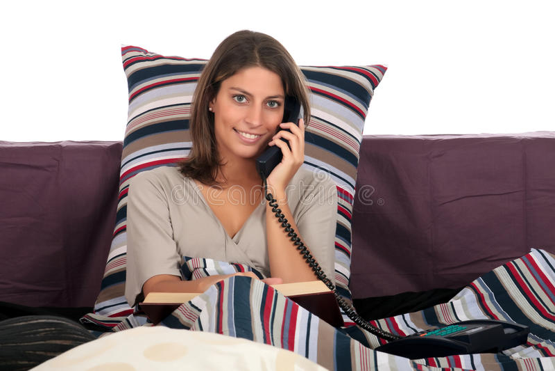 Llamada de teléfono de la cama de la mujer foto de archivo