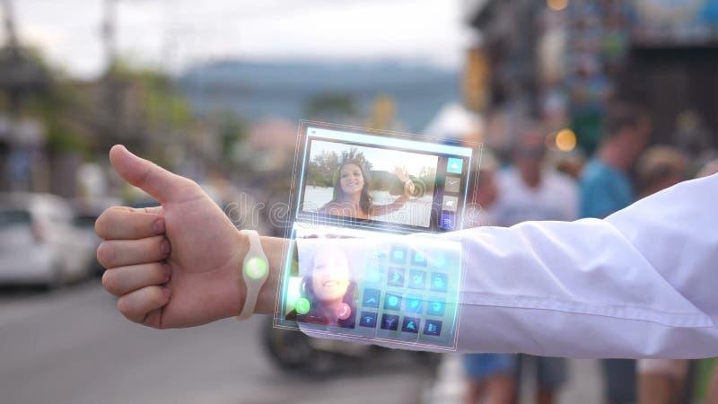Llamada del hombre de negocios la esposa bonita que sonríe y agita la mano del teléfono que aparece en reloj futurista del hologr foto de archivo libre de regalías