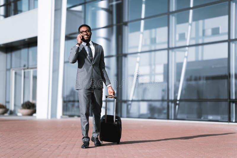 Llamada del taxi Hombre de negocios Arriving At Airport, caminando al aire libre foto de archivo libre de regalías