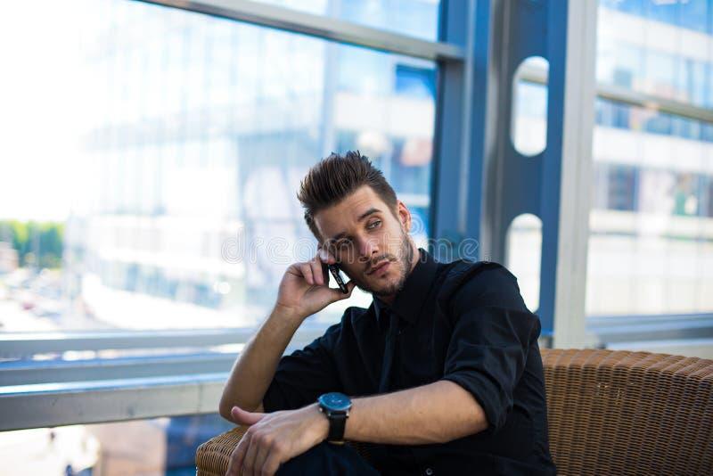 Llamada masculina vía el teléfono móvil mientras que espera la reunión con el cliente imagen de archivo libre de regalías