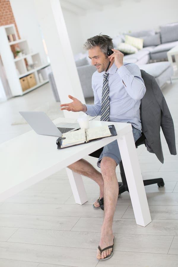 Llamada video del negocio relajado que se encuentra en casa imagen de archivo