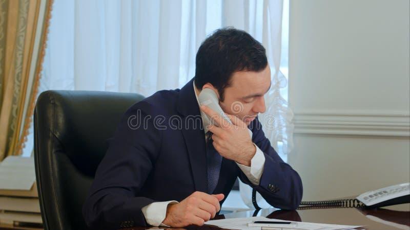 Llamada y comienzo del final del hombre de negocios que trabajan con los documentos en oficina imágenes de archivo libres de regalías