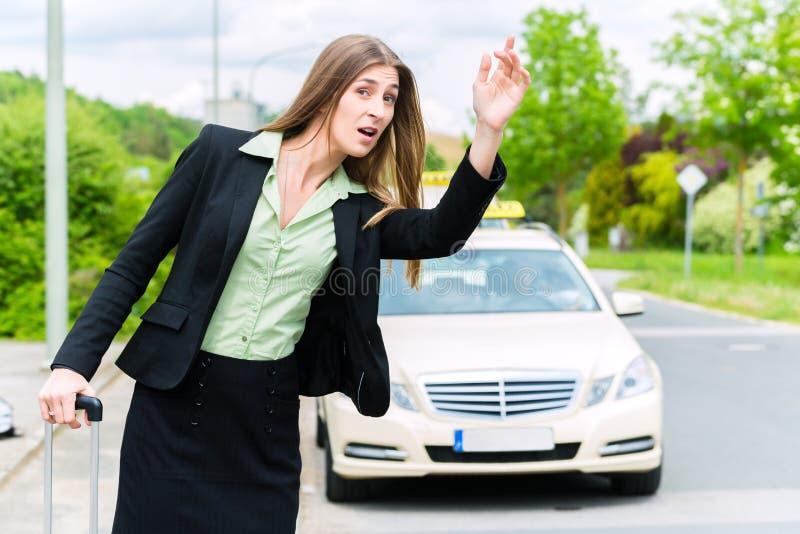 Llamadas jovenes de la empresaria para un taxi fotos de archivo libres de regalías