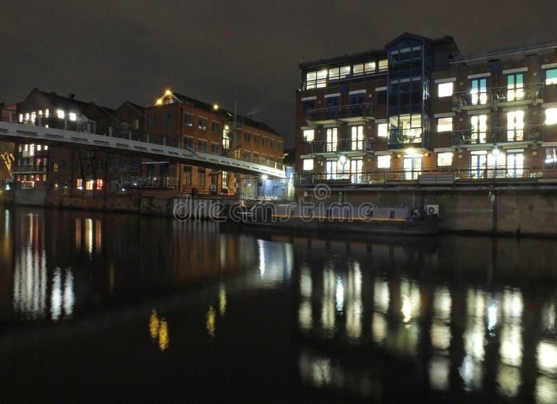 llamadas que aterrizan en el río Aire en Leeds en la noche con las luces de edificios viejos históricos y los apartamentos reflej fotografía de archivo