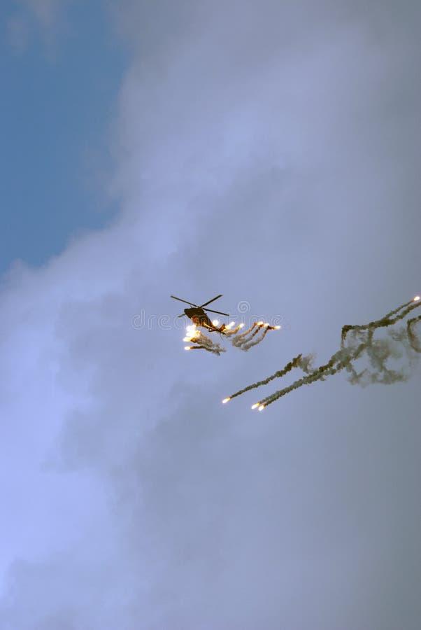 Llamaradas del tiroteo del helicóptero imagenes de archivo