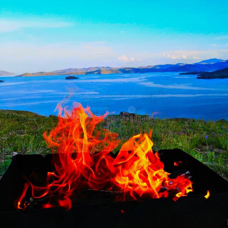 Llamas anaranjadas, un fuego que quema en una rejilla negra del hierro contra el lago foto de archivo libre de regalías