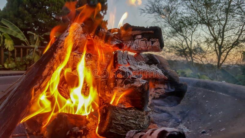 Llamas que queman brillantemente en un hoyo del fuego con puesta del sol en fondo imagen de archivo
