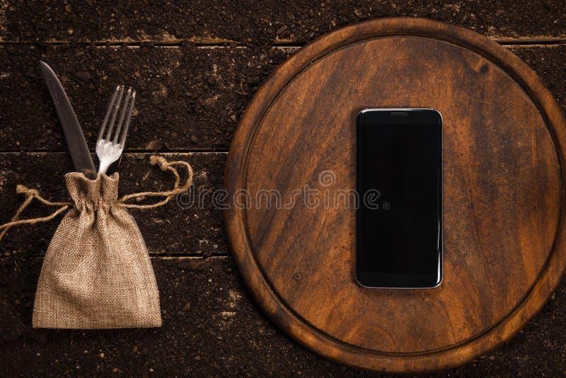 Llame por teléfono en la tabla y la tabla de cortar rústicas con la bifurcación y un cuchillo imagenes de archivo