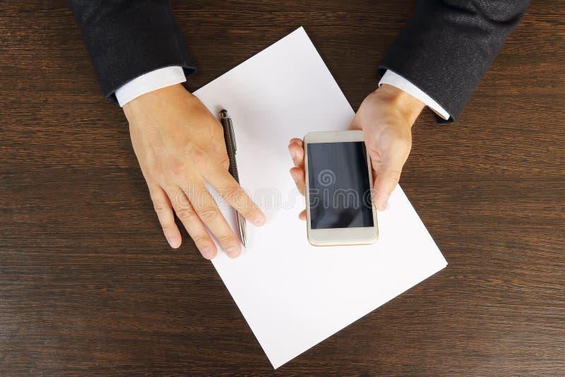 Llame por teléfono en las manos de un hombre de negocios en el primer de escritorio, visión superior imagen de archivo libre de regalías