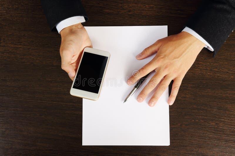Llame por teléfono en las manos del hombre de negocios en el primer de escritorio, visión superior foto de archivo libre de regalías