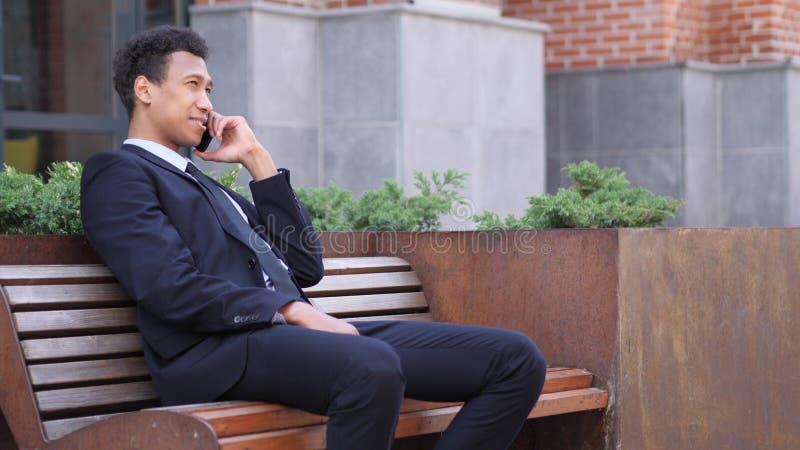 Llame por teléfono a la charla, hombre de negocios africano Attending Call mientras que se sienta en banco imagen de archivo