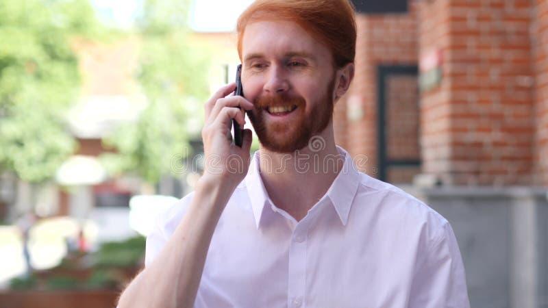 Llame por teléfono a la charla, hombre que asiste a llamada mientras que coloca el edificio exterior foto de archivo