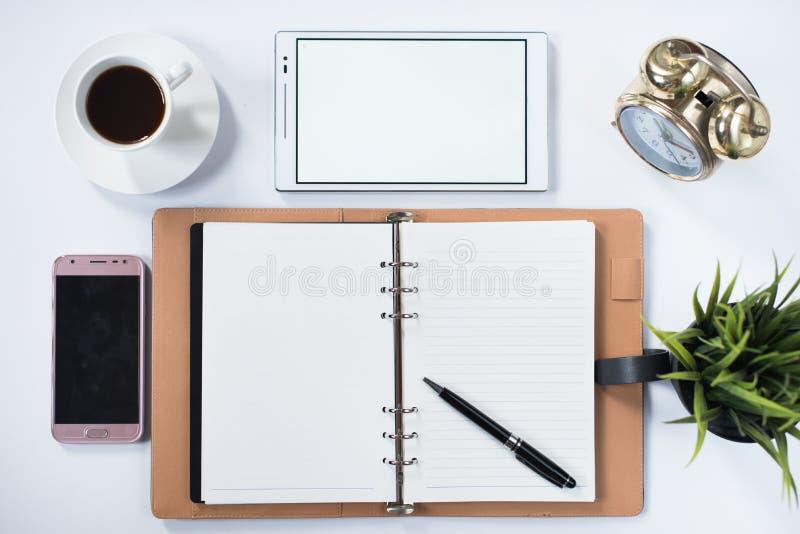 Llame por teléfono, tableta digital, reloj, planta, cojín de nota y esconda el cuaderno con en la endecha blanca del plano imagenes de archivo
