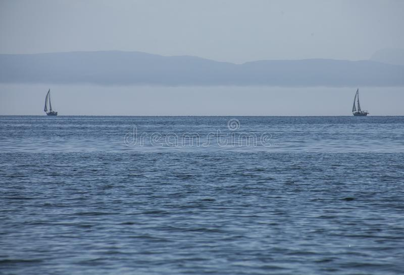 Llanbedrog, Gales norte, o Reino Unido - o mar azul e dois barcos foto de stock royalty free
