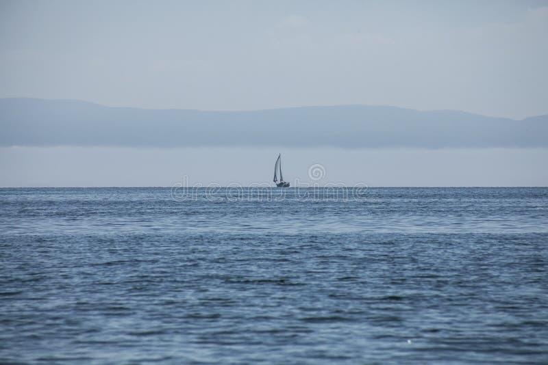 Llanbedrog, Gales norte, o Reino Unido - o mar azul e um barco imagens de stock